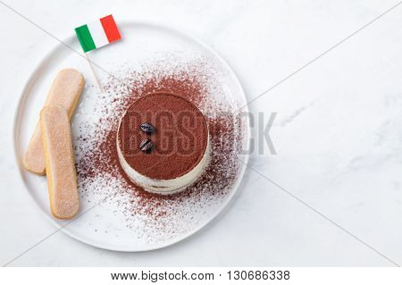 Tiramisu, traditional Italian dessert on a white plate with Italian flag Top view Copy space.