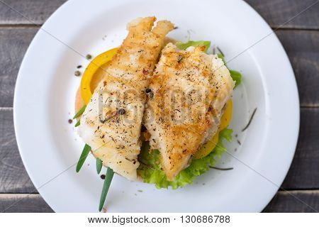 Grilled fish with vegetables on bread on the plate