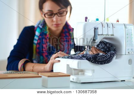 Young woman sewing while sitting at her working place .