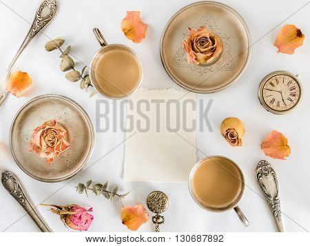 Two cups of coffee with roses, empty card and watch. Flat lay. Top view
