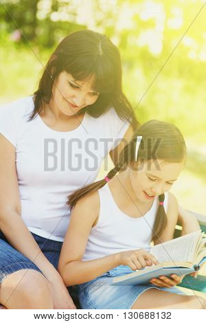 mother with her daughter reading a book in the park