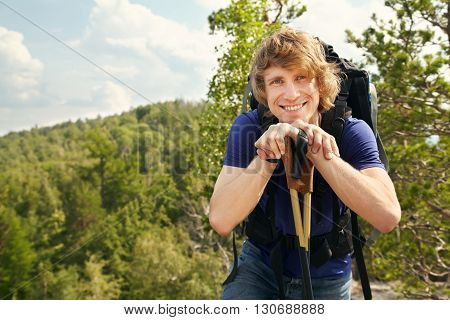 happy young man with backpack hiking in the mountains. sport outdoors
