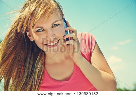 young smiling woman talking on mobile phone on blue sky background. girl with a smartphone