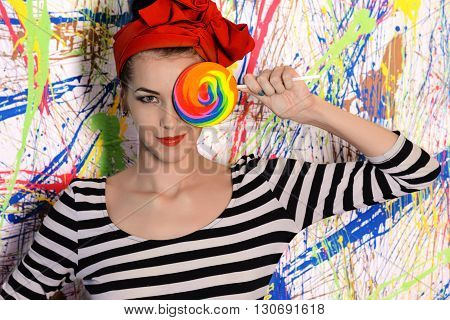 portrait of beautiful girl with big lollipop at wall with different color splash