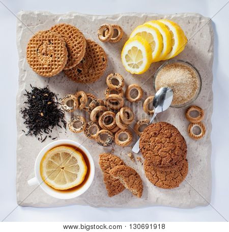 Tea with a lemon  and cookies on a table with bright lighting