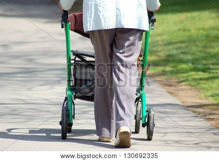 Elderly lady walking in the neighborhood with her walker