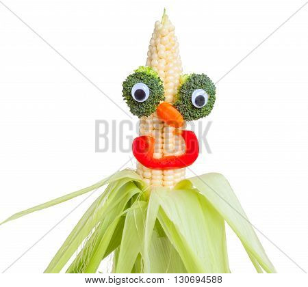 Funny face made from white corn broccoli carrot bell red pepper. Isolated on white. Concept healthy tasty fun vegeterian and vegan food. Green broccoli cabbage mini carrots cayenne maize. Humorous creative. Yellow open ear of corn cut out