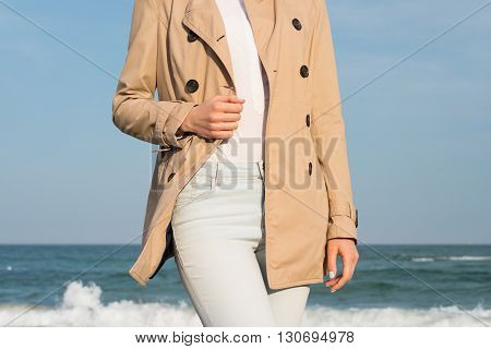 Slender Woman In Coat And Jeans Walking Along The Coast In The Evening Sun