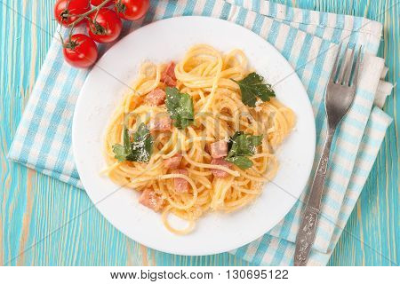 Pasta Carbonara with ham and cheese on blue wooden table. Top view.