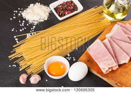 Ingredients for Pasta Carbonara on dark slate background. Top view.