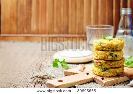 Cheesy millet zucchini fritters on dark wooden background.