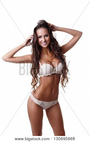 Studio photo of tanned brunette posing in sexy underwear