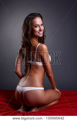 Studio photo of underwear model sitting cross-legged