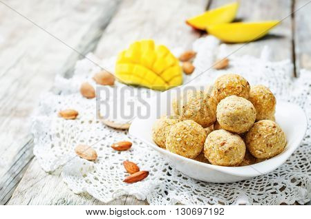raw vegan mango coconut almond balls on wooden background