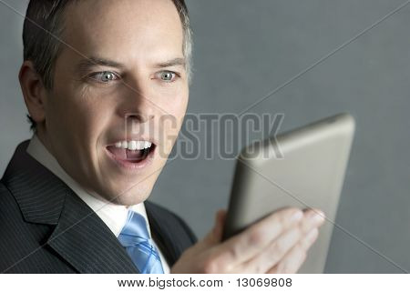 Businessman Looks At Tablet With Pleased Surprise