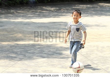 Japanese boy playing with soccer ball (first grade at elementary school)
