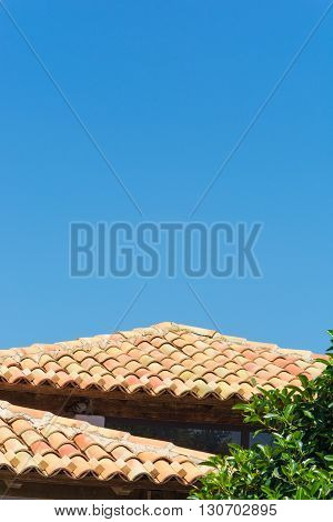 Typical tiled roof. With blue sky and green tree. Background for graphic resources. Typical of the province of Ragusa places of Montalbano. Holiday sights and cultural tourism.