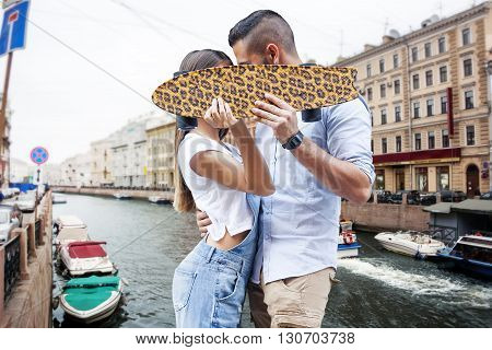 Young Couple Kissing Hiding Behind A Skateboard