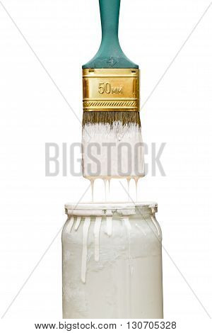 Brush over the bank with a white paint isolated on white background. Drops of paint flow from the brush in a jar.