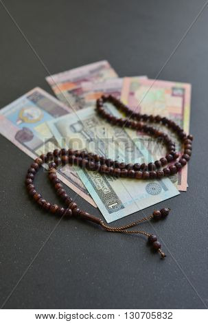 Kuwaiti Dinar currency notes and Islamic prayer beads. Sharia'h or Islamic banking.