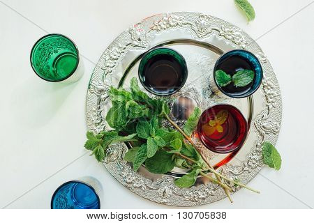 Local favorite Moroccan mint tea. Typical moroccan tea glasses with fresh mint leaves in silver tray. View from above.