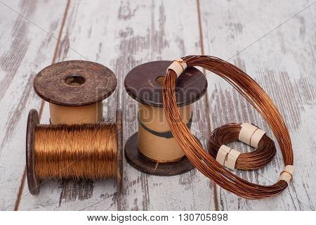 Set of copper wires. Copper wire on the spools and rolls on the old planks.