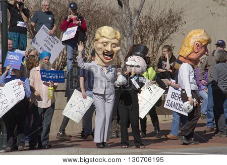 Asheville, North Carolina, USA - February 28, 2016: Effigies of Hillary Clinton Donald Trump and Mr. Monopoly hold bags of money as a crowd of Bernie Sanders supporters holding signs watch at a Bernie Sanders campaign rally