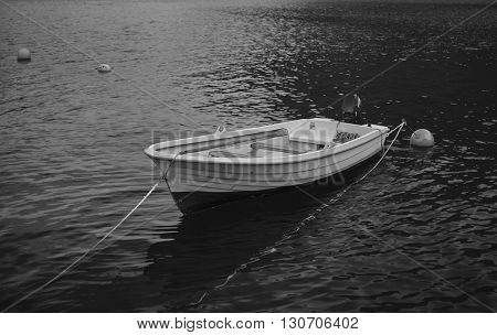 An empty boat on the calm water of a fjord.
