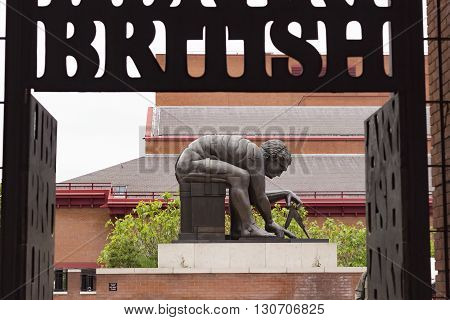 London England - May 19 2016: Entrance Gate of the British Library and Statue of Isaac Newton by Eduardo Paolozzi in London England.