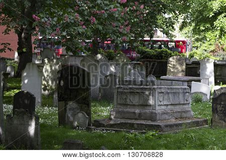 London England - May 19 2016: Bunhill fields burial grounds with two red british bus driving in the background in London England.