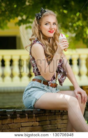 Blonde girl in shorts licking ice cream sitting outdoors