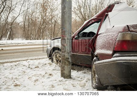 Damaged car crashing side into lamppost in winter.