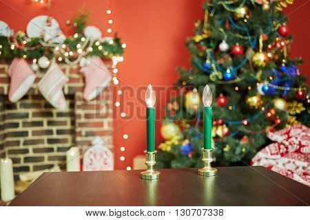 Interior of room with firtree decorated to christmas holidays, fireplace, red walls. Focus  on electric candles at table.