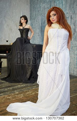 Red-haired woman in white dress and dark-haired woman in black dress in room with old grand piano, focus on red-haired.
