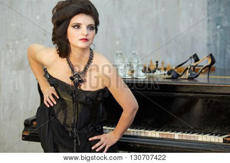 Dark-haired woman in black dress poses standing near old grand piano.