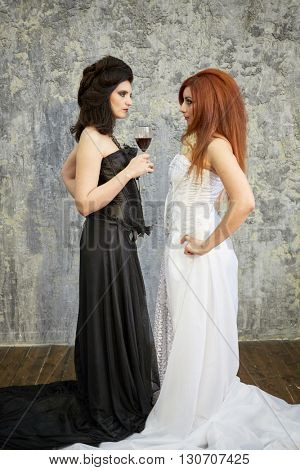 Red-haired woman in white dress and dark-haired woman in black dress stand face to face in room with ragged walls.