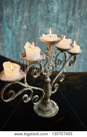Old candlestick with five burning candles stands on surface of grand piano lid.