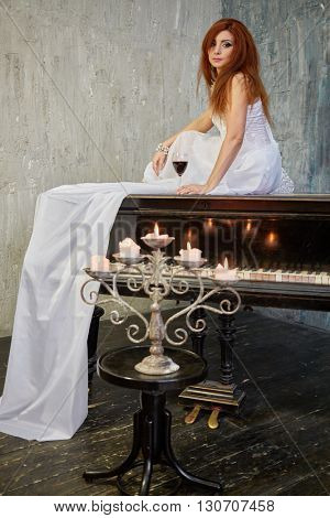 Red-haired woman in white dress sits with glass of red wine on old black grand piano lid, candlestick with burning candles on piano-stool.