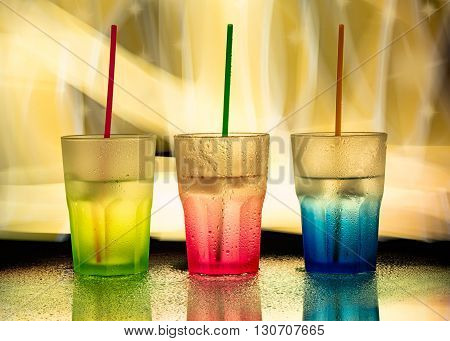 three colored glasses on yellow light background