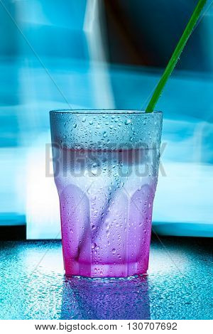 wet glass with green straw on blue light