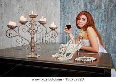 Red-haired woman in white dress stands leaning her elbows on grand piano lid with glass of red wine.