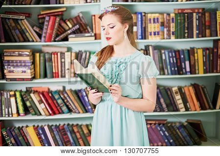 Young woman in green dress reads book, standing at library.