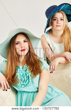 Two young blond women in wide-brimmed hats in studio.