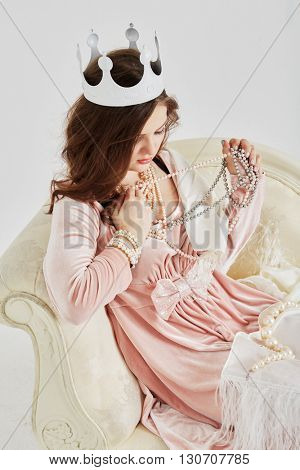 Young woman in pink dress with pearl necklace, beads and crown on head sits on couch.