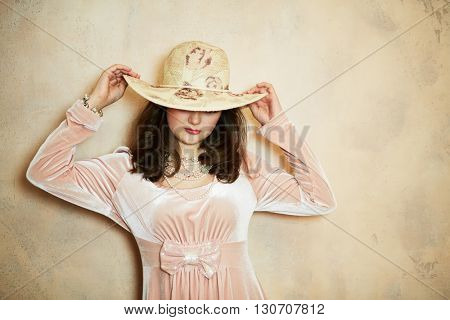 Young woman in pink dress with pearl necklace, beads and wide-brimmed hat on head at wall in studio.