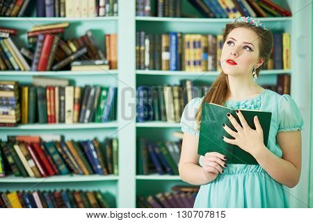Young woman in green dress stands at library holding book.