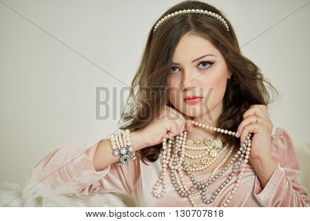 Young woman in pink dress with pearl necklace and diadem in hair.