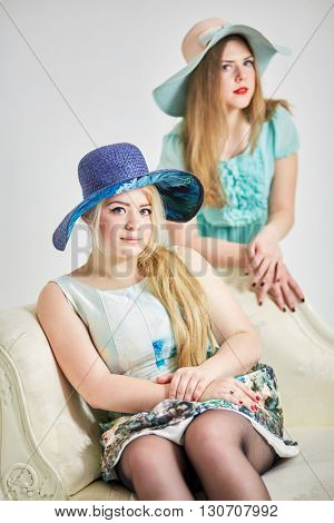 Two young blond women in wide-brimmed hats in studio, focus on first girl.