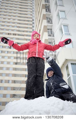 Boy and girl play on snow pile at courtyard near residential hous.