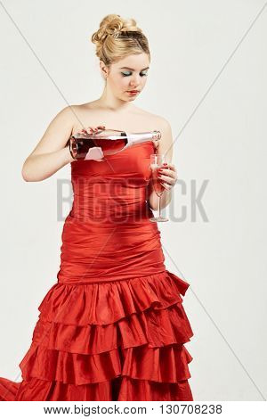 Woman in red dress pours wine from the bottle into the wineglass.
